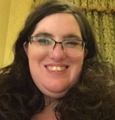 head shot of Karen - wearing glasses, wide smile and lots of bouncy hair